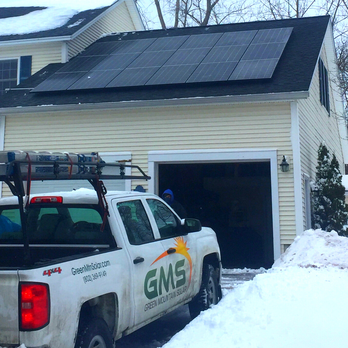 solar panels on garage roof in Vermont with Green Mountain Solar truck